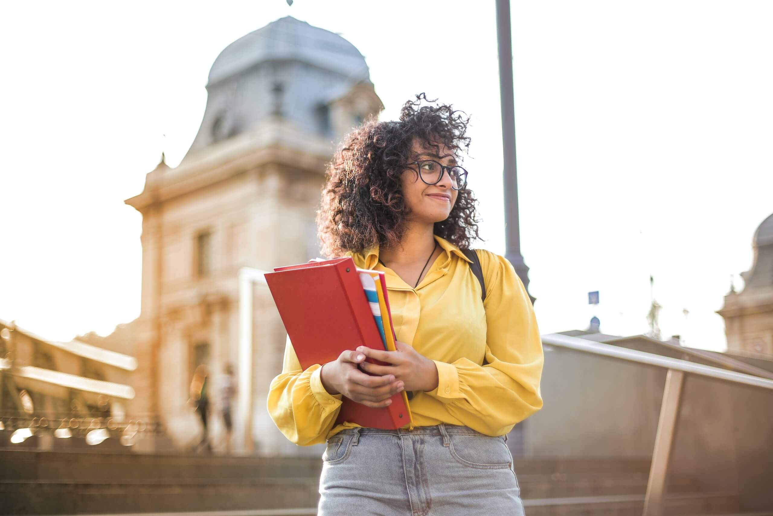 woman in yellow jacket holding red book 3762800 scaled
